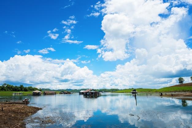 A casa de jangada à beira-mar é cercada por fundo de céu azul, província de kanchanaburi, tailândia