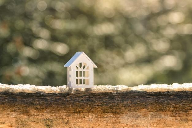 A casa de madeira branca do brinquedo está na neve em um log.