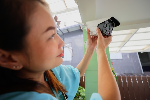 A casa de mulher bonita ajusta a visão do ângulo de direção da câmera de segurança doméstica cctv e a câmera de internet de ajuste fino para uma cena perfeita de assistir. conept para o trabalho autossuficiente e diy de dona de casa moderna.