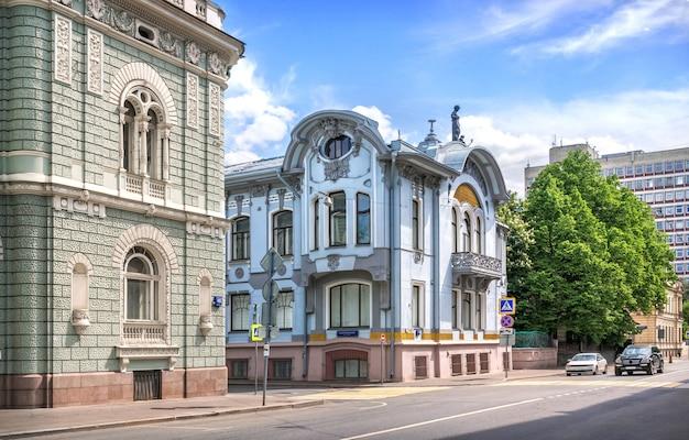 A casa de schlossberg e a mansão de mindovsky na rua povarskaya em moscou em um dia ensolarado de verão. legenda: pista de skaryatinsky