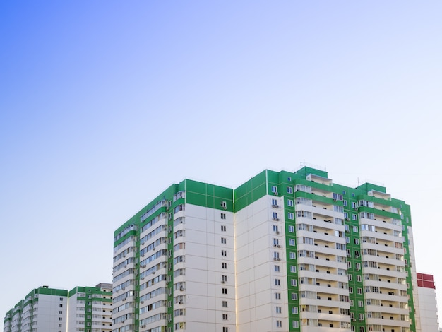 A casa de vários andares é verde contra um céu azul claro