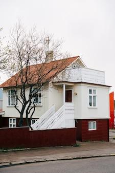 A casa é de cor creme com um telhado laranja, grades brancas nas escadas antes de entrar