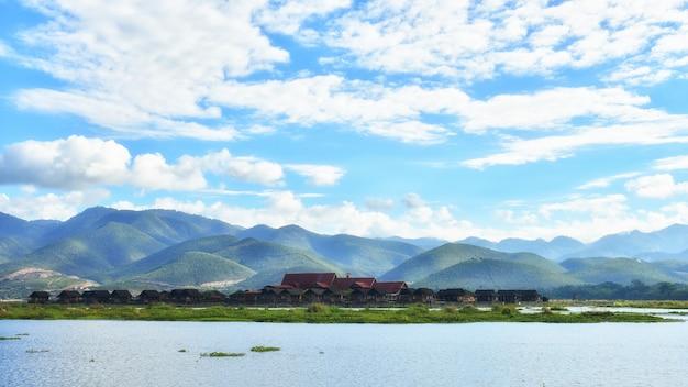A casa flutuante de pessoas inle no lago inle, com um lindo céu, pode usar o inimigo para promover o turismo na vila inla em mianmar.