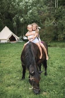 A cavalo, duas crianças meninas, irmãs, andar a cavalo ao ar livre