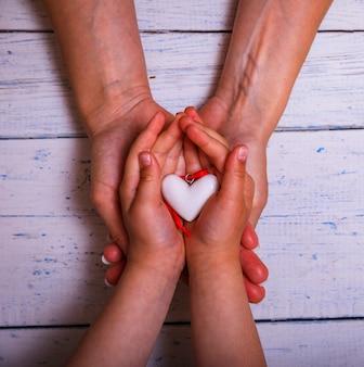 A celebração do dia das mães com mulher pai mantém as mãos da criança apoiando o coração, doação para amamentação e adoção de crianças dos pais, conceito de cuidados de saúde familiar.