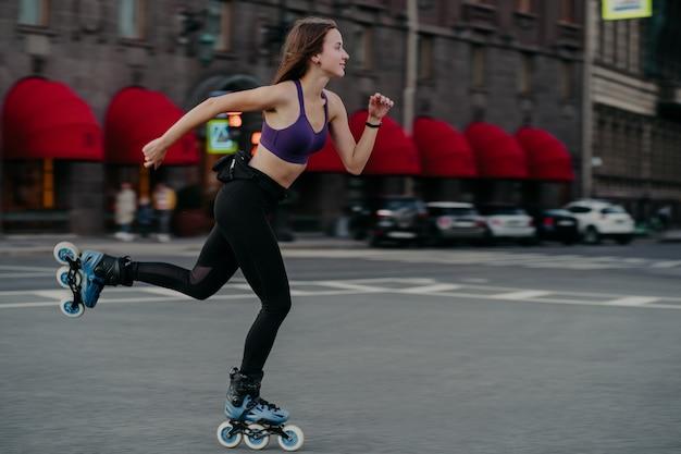 A cena horizontal de uma jovem esguia ativa andando rápido em patins melhora o equilíbrio, agilidade e coordenação, vestida com tops recortados e leggings na rua com foco na distância