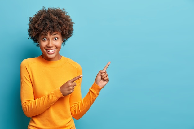 A cena horizontal de uma linda mulher de cabelos cacheados aponta para um espaço de cópia da parede azul indica para publicidade e pede, não apenas passe por sorrisos vestidos de forma casual e alegre, dando a direção certa