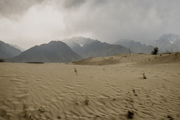 A cena nebulosa e empoeirada após a tempestade no deserto de katpana com neve tampou montanhas na escala do karakoram, paquistão.