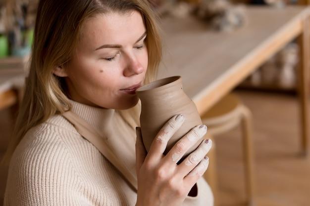 A ceramista está cheirando a argila úmida do vaso recém-feito e cheira a um rio