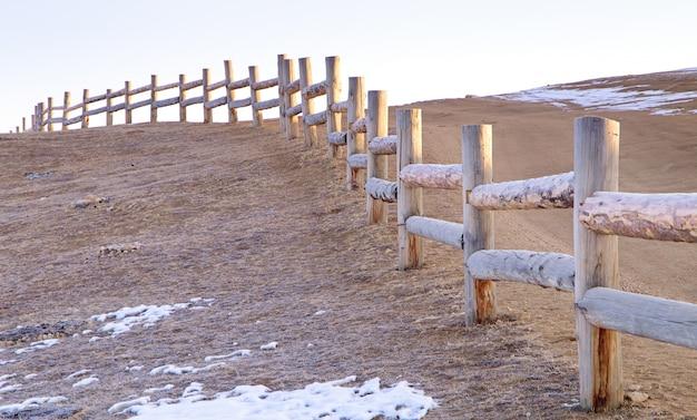 A cerca velha feita de entra o tempo de inverno com neve no chão. ilha olkhon, lago baikal na rússia