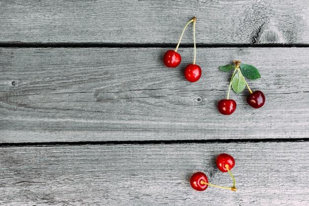 A cereja doce suculenta madura vermelha encontra-se no vintage de madeira.