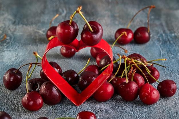 A cereja fresca ou a cereja doce com água deixam cair com um coração vermelho. conceito para dia dos namorados