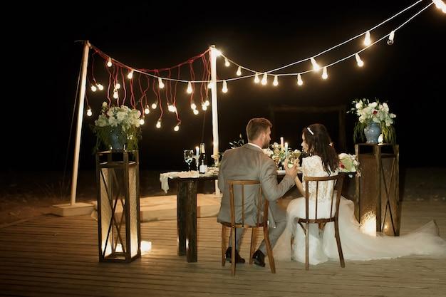 A cerimônia de casamento à noite. a noiva e o noivo estão sentados à mesa festiva. banquete