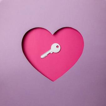 A chave branca está localizada em uma cavidade rosa em forma de coração. tudo ao redor é roxo. copie o espaço. amor. segurança. bloqueado.