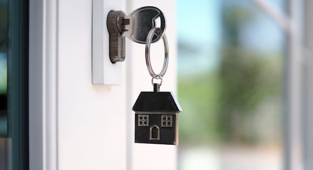 A chave da casa para desbloquear uma nova casa está conectada à porta.