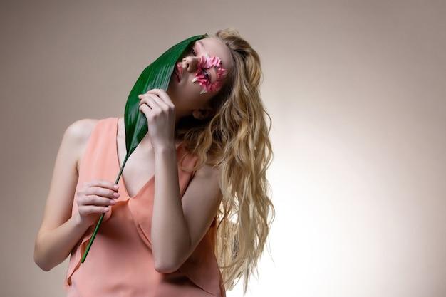 A cheirar a folha verde. jovem modelo profissional de cabelos loiros se sentindo bem enquanto cheira a folha verde