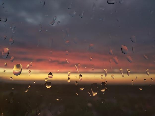 A chuva cai no vidro da janela após o tempo tempestuoso. ver no pôr do sol turva colorido através das gotas de chuva. lindos reflexos em gotas de água na janela. céu dramático depois da chuva