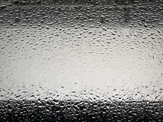 A chuva cai no vidro da janela da cidade.