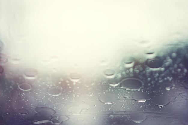 A chuva cai no vidro.