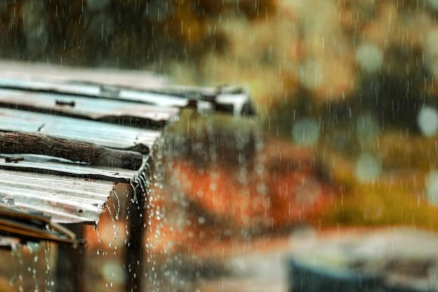 A chuva flui para baixo de um telhado de zinco