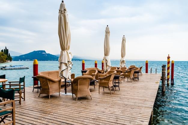 A chuva molha as mesas e cadeiras de um restaurante sem clientes em um lago italiano para turistas.