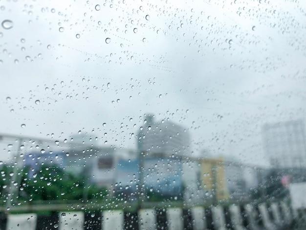 A chuva no carro espelho com fundo do local de construção.