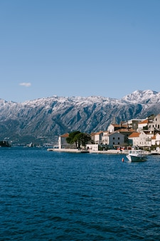 A cidade de perast tendo como pano de fundo montanhas cobertas de neve