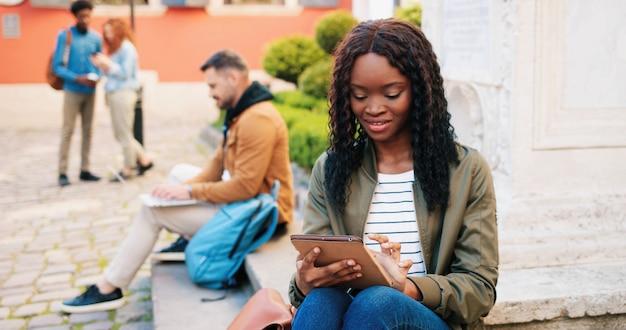A cidade vibra uma estudante multirracial elegante usando seu computador tablet enquanto desfruta de um retrato de rua ...