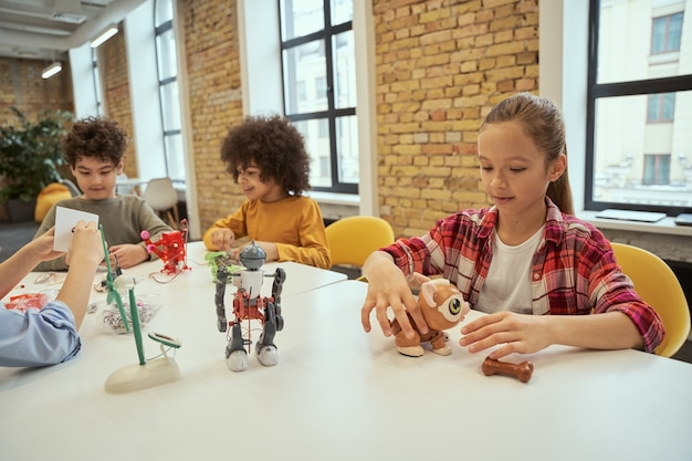 A ciência está em toda parte positiva, crianças diversificadas que passam o tempo na menina do clube de engenharia sentada