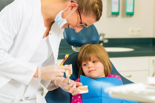 A cirurgia de dentista mantém a dentadura e explica uma criança doente com uma escova de dentes