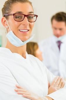 A cirurgia de dentista, olhando para o espectador, em seu colega, está dando tratamento a uma paciente do sexo feminino
