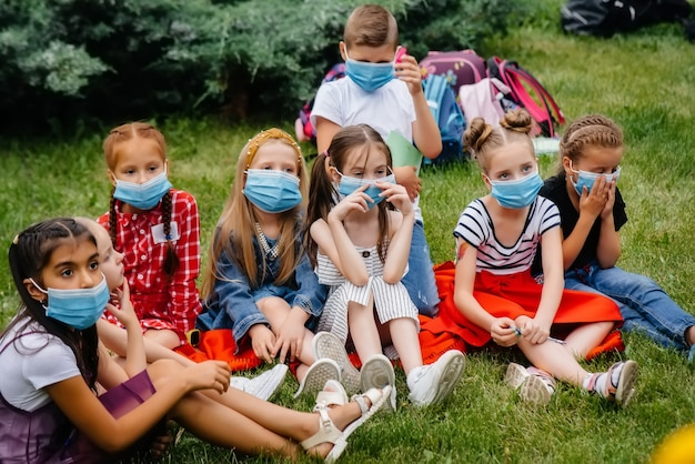 A classe de alunos mascarados está envolvida em treinamento ao ar livre durante a epidemia