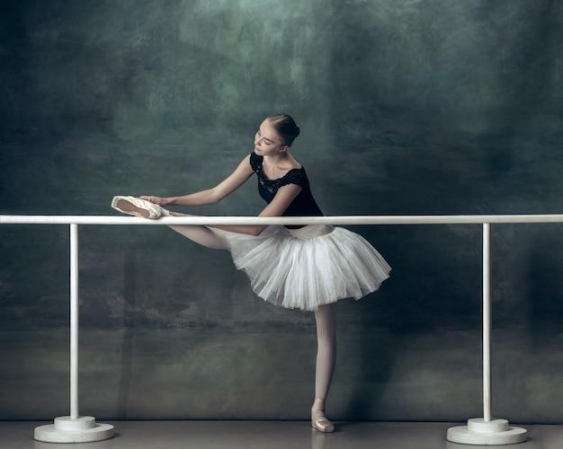 A clássica bailarina posando na barra de balé