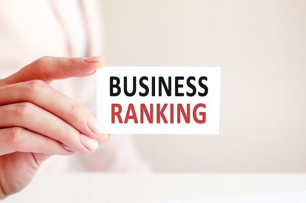 A classificação de negócios é escrita em um cartão branco na mão de uma mulher.
