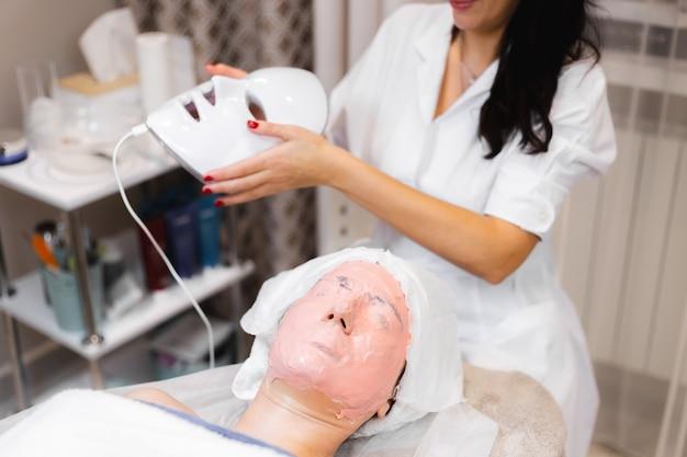 A cliente encontra-se no salão, na mesa de cosmetologia, com uma máscara branca no rosto