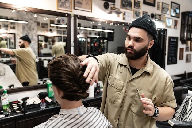 A cliente recebe corte e modelagem de cabelo em salão de beleza. barber atende o cliente.