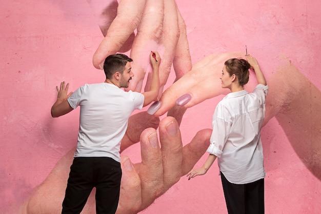 A colagem sobre um casal escrevendo algo em uma parede rosa. na parede minha foto de mãos femininas e masculinas. conceito de amor e nova família