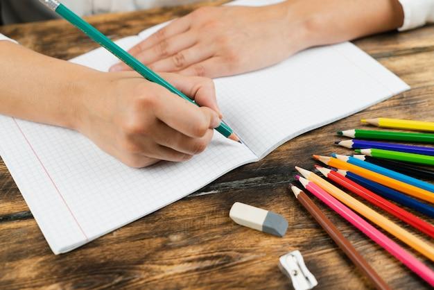 A colegial se senta em sua mesa e desenha em um caderno com lápis de cor.