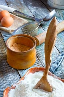 A colher de pau preso à tigela de cerâmica com a farinha, um frasco com sal, ovos, rolo de massa