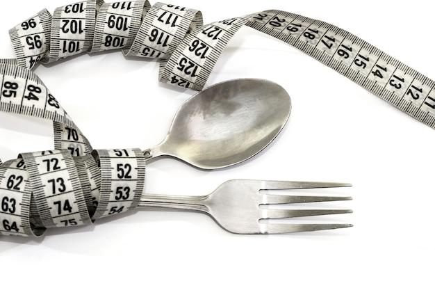 A colher e o garfo estão envolvidos em uma fita métrica