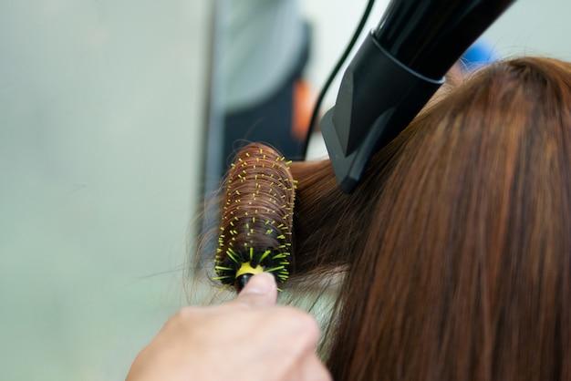 A coloração de cabelo e estilo de ajuste de permanente encaracolado no salão de beleza faz o cabelo danificado e grosso