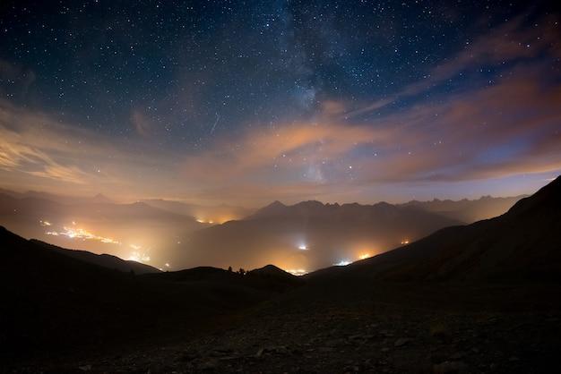 A colorida via láctea brilhante e o céu estrelado sobre os alpes franceses e o majestoso maciço dos ecrins.