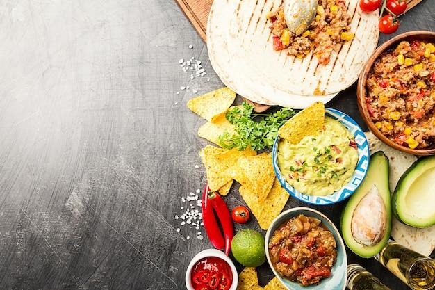 A comida mexicana mistura nachos, fajitas, tortilla, guacamole e molhos salsa e ingredientes sobre uma superfície preta. vista superior com espaço de cópia