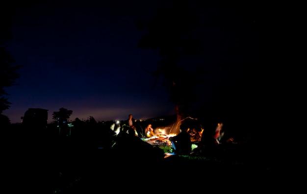 A companhia de jovens está sentada ao redor da fogueira e cantando canções