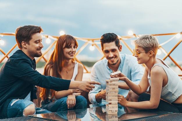 A companhia de jovens jogando jogo de tabuleiro