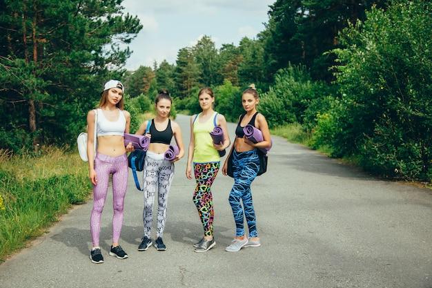 A companhia de jovens mulheres atraentes amigos com equipamentos esportivos, indo para um treino no parque.