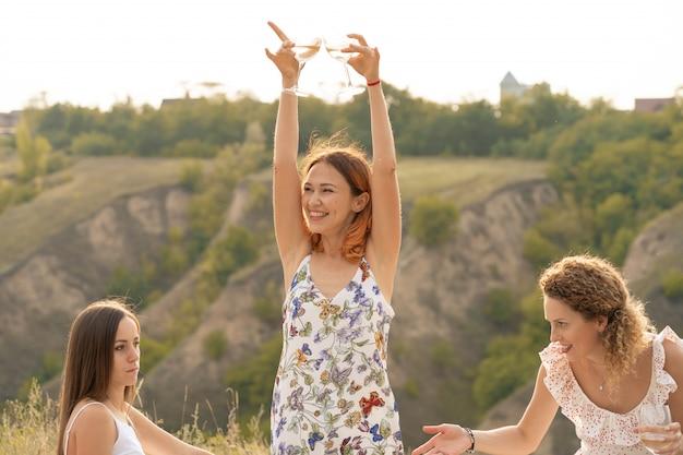 A companhia de lindos amigos se divertindo, bebendo vinho e desfrutando de um piquenique nas montanhas
