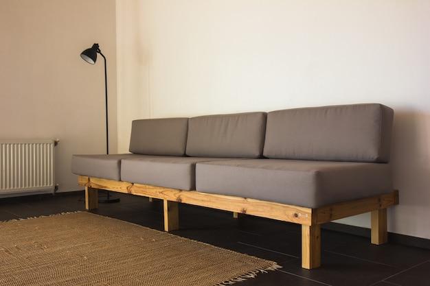A composição boho elegante no interior da sala de estar com sofá cinza design, mesa de café de madeira, vaso sanitário e acessórios pessoais elegantes. almofada e manta amarelo mel. apartamento acolhedor. decoração de casa