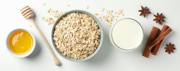A composição com farinha de aveia lasca-se na vista branca, superior. cozinhando o café da manhã