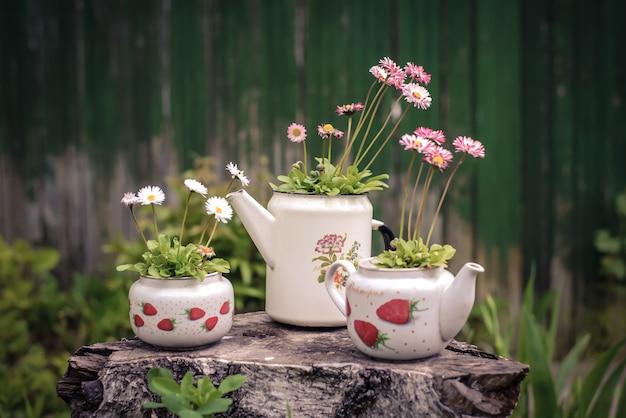 A composição da chaleira branca velha, telefone, vaso com flores